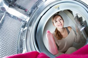 Housework: young woman doing laundry (shallow DOF; color toned i